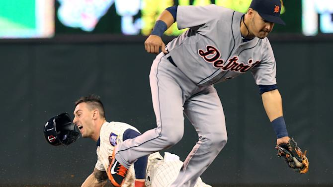 Minnesota Twins' Jordan Schafer, left, loses his helmet as he steals third on Detroit Tigers shortstop Eugenio Suarez in the eighth inning of a baseball game, Wednesday, Sept. 17, 2014, in Minneapolis. The Twins won 8-4. (AP Photo/Jim Mone)
