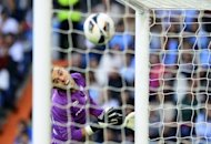 Celta&#39;s goalkeeper Sergio Alvarez eyes the ball as Real Madrid&#39;s forward Gonzalo Higuain scores during their Spanish League football match at the Santiago Bernabeu stadium in Madrid. Real Madrid won 2-0
