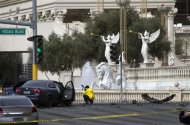 A crime scene analyst photographs a car in front of Caesars Palace hotel-casino after a shooting and multi-car accident that left three people dead and at least three injured on the Las Vegas Strip in Las Vegas, Nevada February 21, 2013. REUTERS/Las Vegas Sun/Steve Marcus