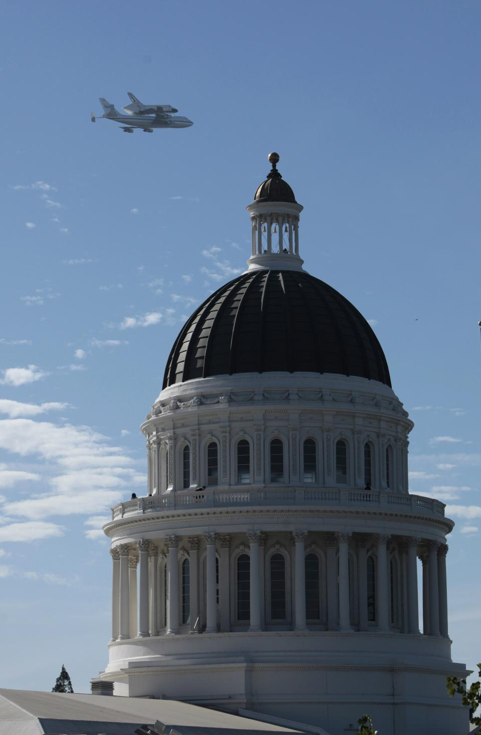 The space shuttle Endeavour passes over the California state Capitol, Friday, Sept. 21, 2012,  in Sacramento, Calif. Endeavour is making a final trek across the country to the California Science Center in Los Angeles, where it will be permanently displayed.(AP Photo/Rich Pedroncelli)