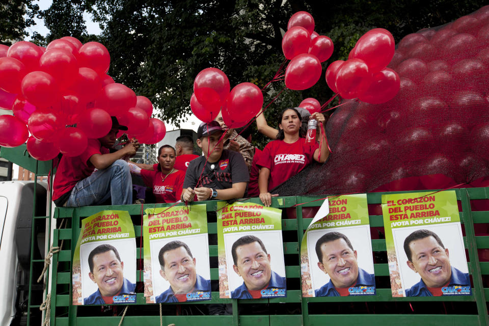 Supporters of Venezuela's President Hugo Chavez stand in a trailer bed as they take part in a campaign caravan through the streets of Caracas, Venezuela, Friday, Sept. 28, 2012. Venezuela's presidential election is scheduled for Oct. 7. (AP Photo/Rodrigo Abd)