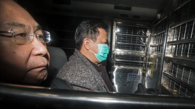 Former Hong Kong Stock Exchange official Francis Kwan  and Hong Kong's former chief secretary Rafael Hui, sit in a prison van as they arrive at the High Court in Hong Kong