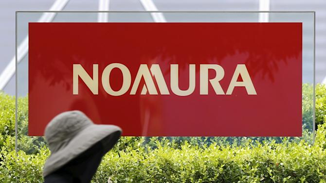 Woman cycles past a sign of Nomura Holdings in Tokyo