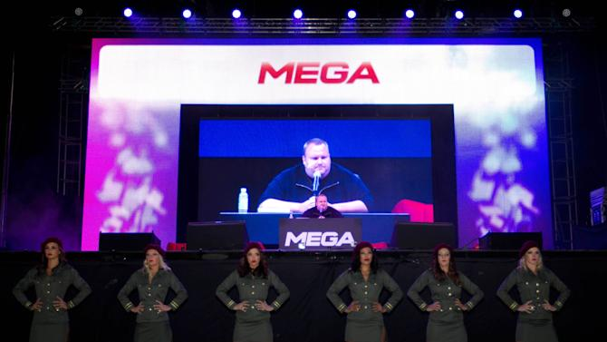 "Indicted Megaupload founder Kim Dotcom appears on a large screen during the launch of a new file-sharing website called ""Mega"" at his Coatesville mansion in Auckland, New Zealand, Sunday, Jan. 20, 2013. The colorful entrepreneur unveiled the site ahead of a lavish gala and press conference on the anniversary of his arrest on racketeering charges related to his now-shuttered Megaupload file-sharing site. (AP Photo/New Zealand Herald, Richard Robinson) New Zealand Out, Australia Out"
