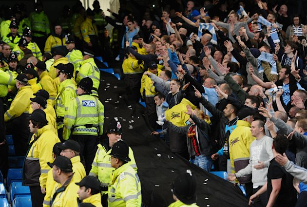 Manchester City Fans (R) Gesture Towards Manchester United Fans 