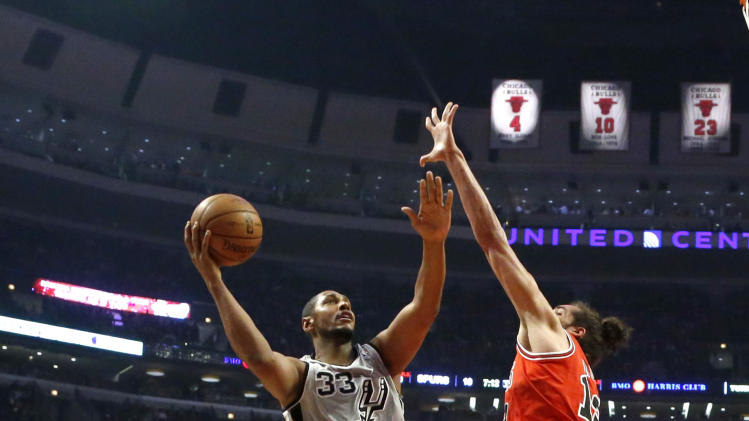 San Antonio Spurs center Boris Diaw (33) shoots over Chicago Bulls center Joakim Noah (13) as forward Luol Deng watches during the first half of an NBA basketball game, Monday, Feb. 11, 2013, in Chicago. (AP Photo/Charles Rex Arbogast)