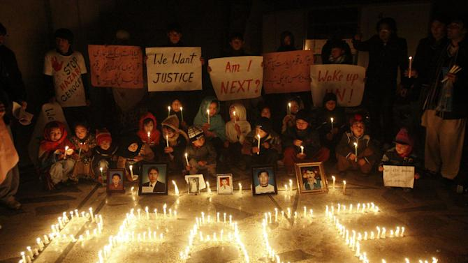 In this Thursday, Feb. 21, 2013, photo, Pakistani Shiite Muslim children hold candles and banners next to photographs of people, who were killed by a bomb blast in market on Saturday, February 16, 2013, in Quetta, Pakistan. Terrorized by ferocious attacks that have killed nearly 400 ethnic Hazaras in the past 18 months, with almost half of those deaths occurring in the first two months of this year, Shiite leaders blamed the inaction of Pakistan's security service for the rising violence against them in Quetta, the capital of southwestern Baluchistan province.(AP Photo/Arshad Butt)