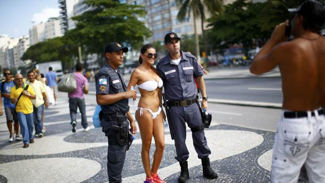 A woman poses with police officers near Copacabana Beach ahead of the 2014 World Cup in Rio de Janeiro