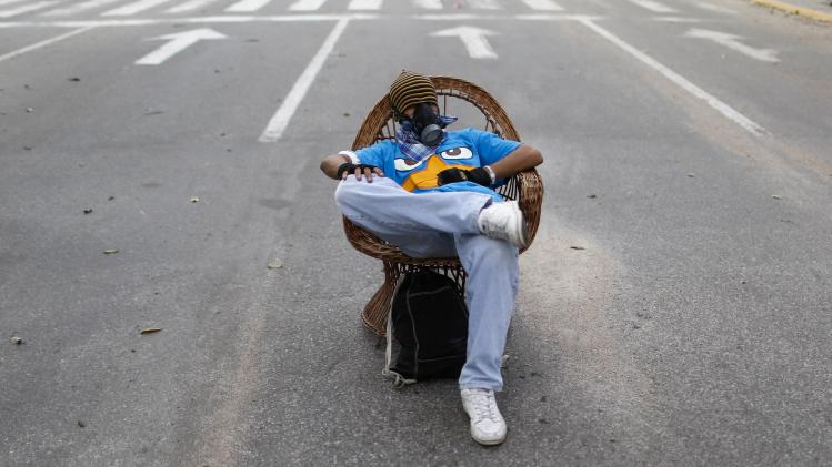 An anti-government protester rests on a chair in the middle of the street during a protest against President Nicolas Maduro's government in Caracas