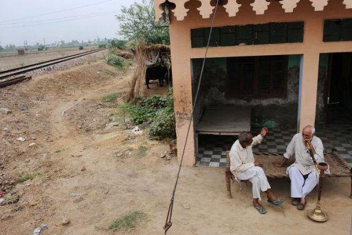 Two men sit near dried out fields in the village of Kherikhummar