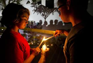 Olina Ortega, left, and Austin Gibbs light candles …
