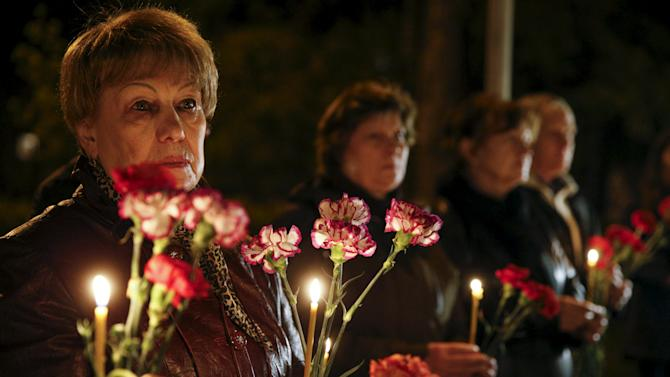 People hold flowers and candles for victims of the Chernobyl nuclear disaster during a memorial service in Kiev