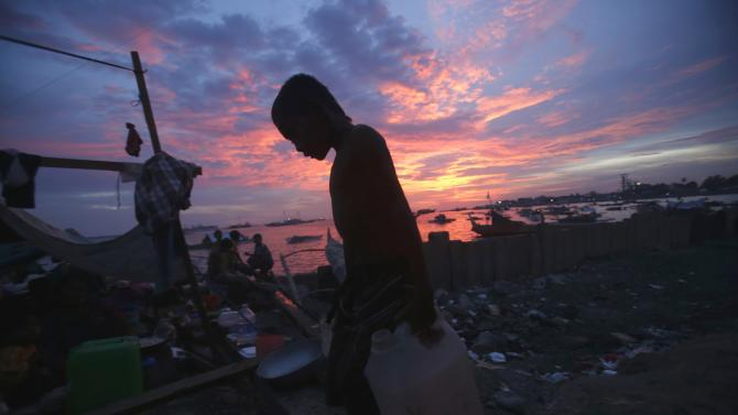 A boy carries drinking water in containers towards makeshift shelters for families displaced in Zamboanga city in southern Philippines