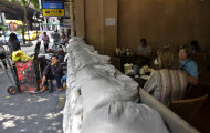 Foreign tourists, right, spend time at a cafe, fortified with sandbags to stop floodwaters, in Bangkok, Thailand, Friday, Nov. 11, 2011. Thailand is once again in tourist turmoil as floods linger, but ever resilient industry unfazed. (AP Photo/Altaf Qadri)