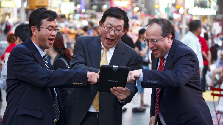 COMMERCIAL IMAGE - From left, Kazuyoshi Onishi, Assistant Vice President, TDK U.S.A. Corporation, Yoshiaki Uchiyama, Vice President, Corporate Communications & CSR and Corporate Planning, Toshiba America Inc., and Jeffrey Straus, President, Countdown Entertainment, use a Toshiba tablet to launch a giant digitally animated fireworks display as it debuts on the Toshiba Vision and TDK screens high atop One Times Square in tribute to Independence Day on Wednesday, June 27, 2012 in New York City. (Photo by Brian Ach/Invision for Toshiba/AP Images)