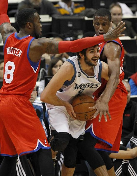 Minnesota Timberwolves guard Ricky Rubio, center, of Spain, is trapped by Philadelphia 76ers guard Tony Wroten (8) and forward Thaddeus Young, right, during the first quarter of an NBA basketball game