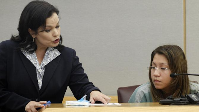 FILE - In a Thursday, Oct. 11, 2012 file photo, prosecutor Eren Price, left, points to a piece of states evidence as she addresses Elizabeth Escalona, 23, during Escalona's sentencing proceedings  in Dallas. Escalona was sentenced Friday, Oct. 12, 2012 to 99 years in prison for beating her toddler and gluing the child's hands to a wall.  (AP Photo/Tony Gutierrez, File)