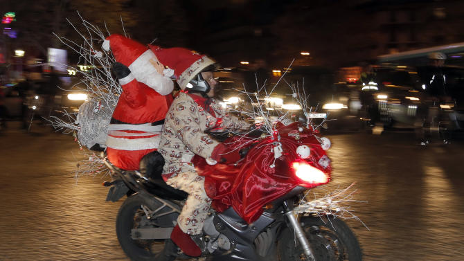 "A biker, dressed as Santa Claus, takes part in the ""Christmas Carabalade"" in the streets of Paris, Thursday, Dec. 18, 2014. Over 1,500 bikers participated in the ride in Paris. (AP Photo/Francois Mori )"