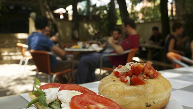 In this Aug. 1, 2014 photo, a plate of pizzella and a half-baguetteare displayed at the Necci bar, a bohemian outpost in Rome's edgy Pigneto neighborhood. Rome is a sightseer's dream, and for many visitors indulging in authentic Italian cuisine is one of the biggest draws. (AP Photo/Kavitha Surana)