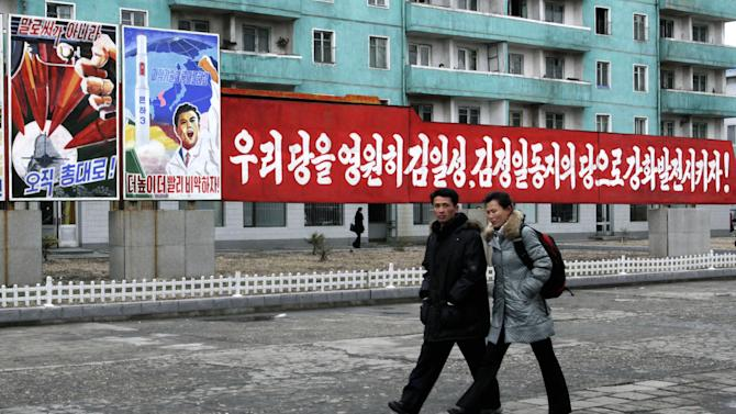 "A couple walks past posters reading ""not with words but with arms,"" left, and ""Higher, faster,"" second from left, as well as a banner reading ""Let's strengthen and enhance our party as the party of Kim Il Sung and Kim Jong Il!""  on a street in Phyongchon District, Pyongyang, North Korea, on Tuesday, March 19, 2013. (AP Photo/Jon Chol Jin)"