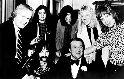 Back row: keyboardist Viv Savage ( David Kaff ) and drummer Mick Shrimpton ( R.J. Parnell )Front row: Spinal Tap manager Ian Faith ( Tony Hendra ), bass player Derek Smalls ( Harry Shearer ), presiden