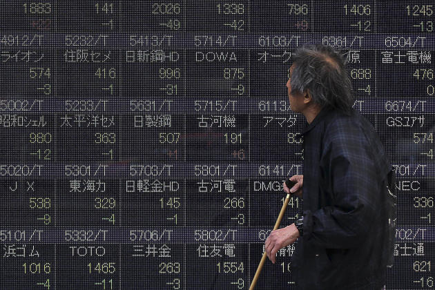A man looks at a stock price chart on a street in Tokyo, Monday, March 10, 2014. Asian stock markets sank Monday, battered by weak Chinese trade and a reduced estimate for Japan's economic growth.