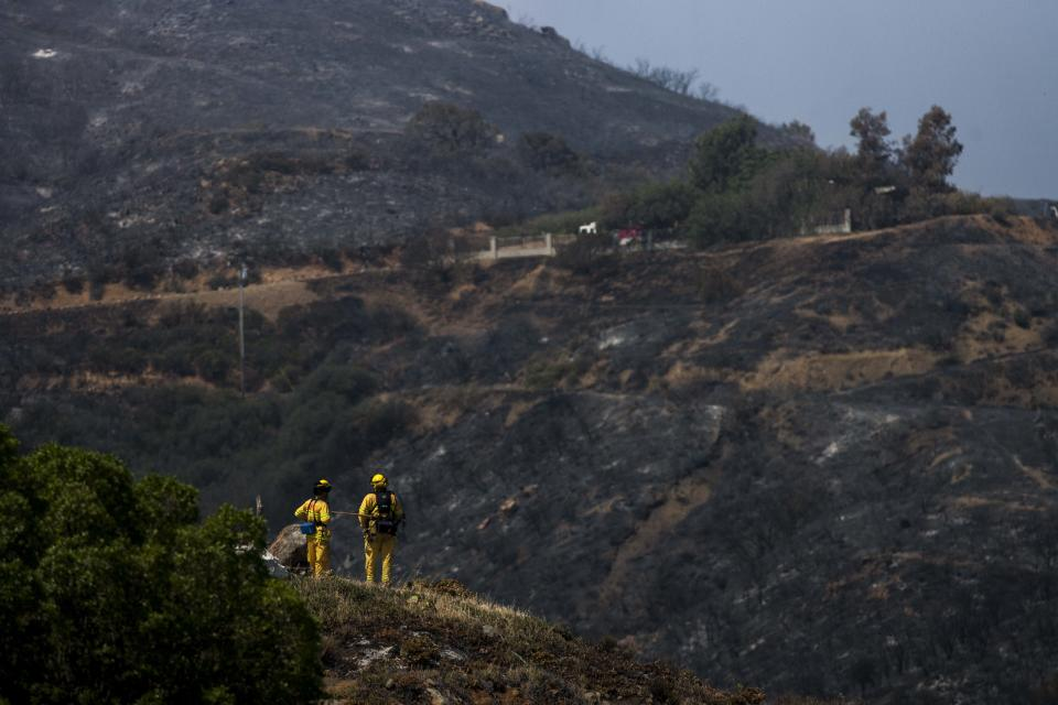 Firefighters keep watch after a wildfire around the burnt area near Point Mugu, Calif., Saturday, May 4, 2013.  High winds and withering hot, dry air was replaced by the normal flow of damp air off the Pacific, significantly reducing fire activity.  (AP Photo/Ringo H.W. Chiu)