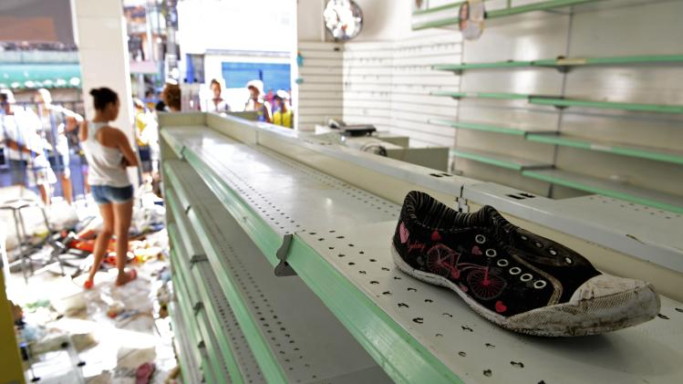 A woman stands inside a store that was looted during a police strike in Salvador