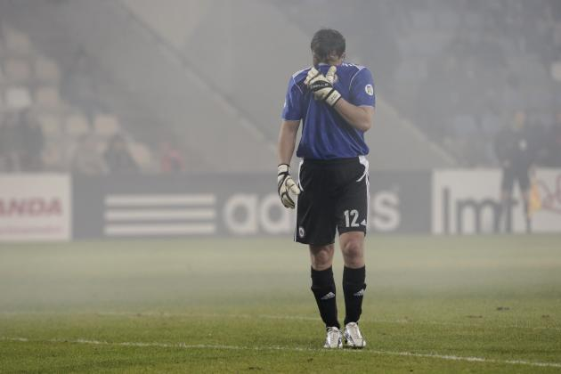 Latvia's goalkeeper Kolinko cover his face from the smoke during their 2014 World Cup qualifying soccer match against Slovakia in Riga