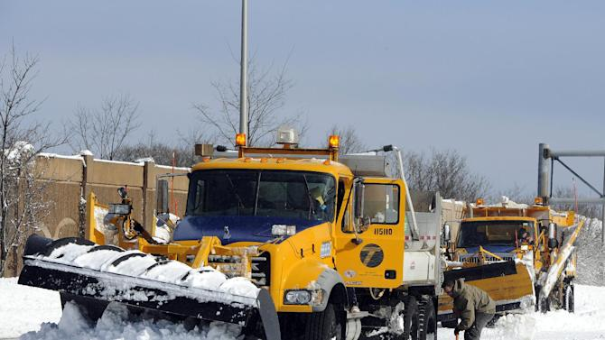 A New York State Department of Transportation plow is dug out of the snow after being stuck near Exit 60 eastbound on the Long Island Expressway after a storm, Saturday, Feb. 9, 2013, in Ronkonkoma, N.Y. (AP Photo/Kathy Kmonicek)