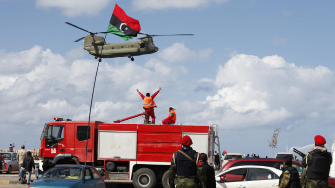 A Libyan military helicopter flies overhead at Tahrir Square during the celebration of the second anniversary of the revolution in Benghazi, Libya, Sunday, Feb, 17, 2013. Libya's interim President Mohammed el-Megarif called on Sunday for unity in the North African nation as it celebrates the second anniversary of the uprising that toppled longtime dictator Moammar Gadhafi but plunged the country into lawlessness and economic woes. (AP Photo/Mohammad Hannon)