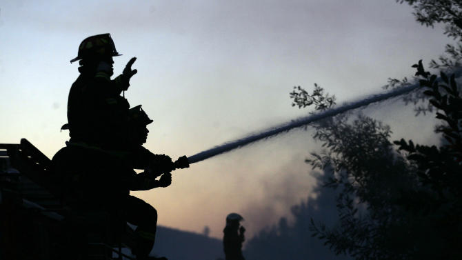 Firefighters spray water into a burning forest in Valparaiso, Chile, Saturday, March 14, 2015. A serious forest fire spread quickly on Chile's coast Friday and threatened to reach the nearby port cities of Valparaiso and Vina del Mar. (AP Photo/Luis Hidalgo)