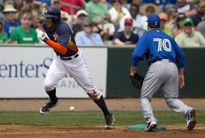 After hitting a two-run triple, Houston Astros' Justin Maxwell, left, sprints for home after a throwing error by Toronto Blue Jays infielder Mike McCoy (not shown) got past Andy LaRoche, right, during the first inning of an exhibition spring training baseball game on Sunday, March 17, 2013, in Kissimmee, Fla. Maxwell scored on the play. (AP Photo/Evan Vucci)