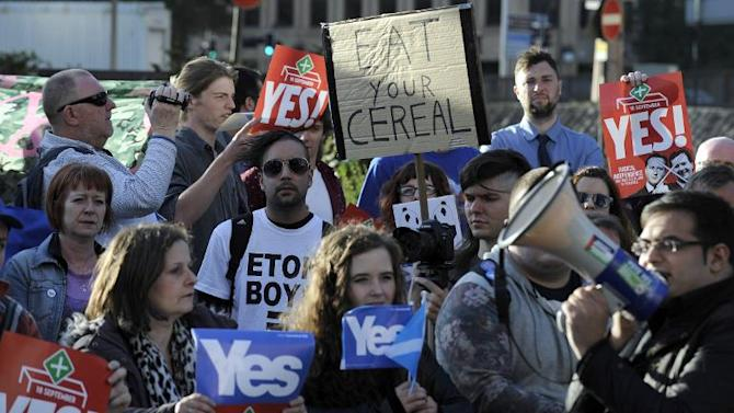 Protesters hold Scottish independence referendum banners from the 'Yes' campaign outside the venue where Britain's Prime Minister David Cameron was to address the CBI Scotland Annual Dinner in Glasgow on August 28, 2014