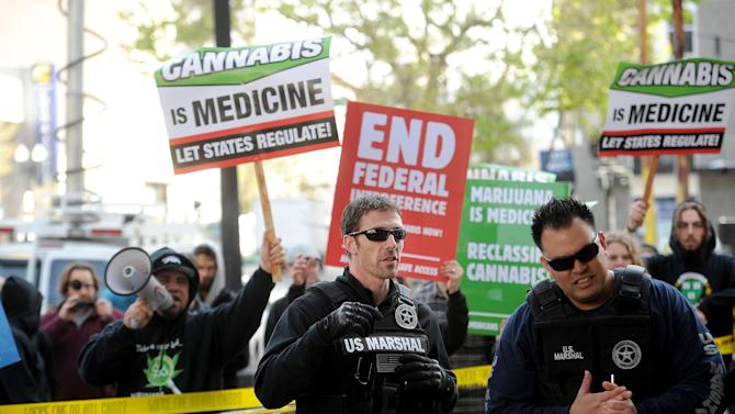 With marijuana proponents chanting behind them, U.S. marshals raid Oaksterdam University in Oakland, Calif., on Monday, April 2, 2012. The facility, one of several that federal agents raided on Monday, teaches people how to grow marijuana. (AP Photo/Noah Berger)