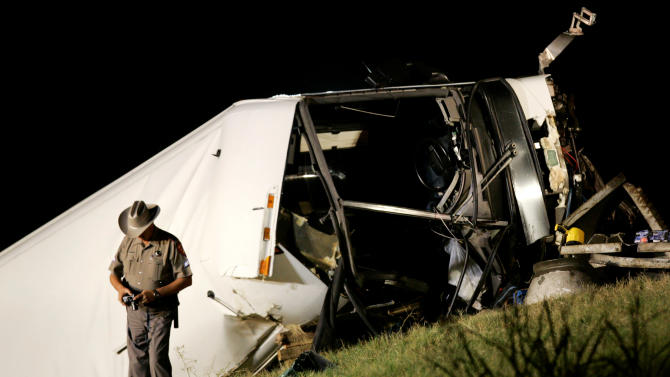 FILE - In this Aug. 8, 2008 photo, A Texas state trooper makes photographs at a bus accident scene on U.S. 75 North bound that killed several people in Sherman, Texas. Months after their state-certified vehicle inspection station was cited by federal authorities for failing to notice defects in a bus that crashed in North Texas, killing 17 passengers, brothers Alam and Cesar Hernandez shuttered their firm. But that didn't mean they were out of the vehicle inspection business. (AP Photo/Tony Gutierrez, File)