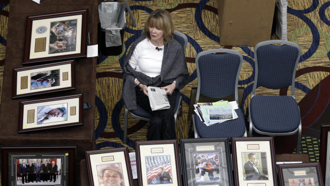 FILE - This Feb. 24, 2012 file photo shows Kay Aaron waiting for customers at a booth selling pictures of Republican leaders and icons during the California Republican Party convention in Burlingame, Calif. If the future happens first in California, the Republican Party has a problem. The nation's most populous state _ home to one in eight Americans _ has entered a period of Democratic political dominance so far-reaching that the dwindling number of Republicans in the Legislature are in danger of becoming mere spectators at the statehouse.  (AP Photo/Marcio Jose Sanchez, File)