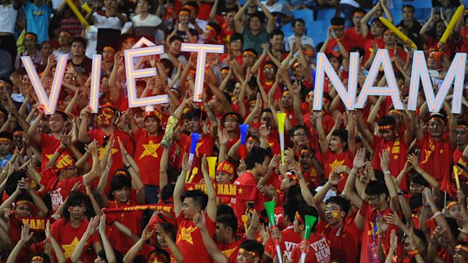Fans of Vietnam cheer for their team during their Suzuki Cup soccer match against the Philippines in Hanoi