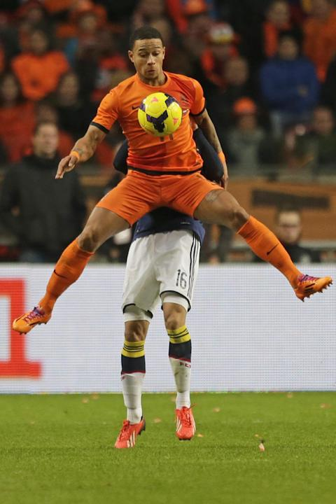 Netherlands' Memphis Depay, foreground, and Colombia's Santiago Arias, rear, vie for the ball during the international friendly soccer match between Netherlands and Colombia at ArenA stadium in Amster