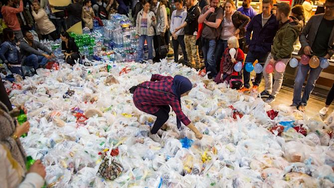 People surround hundreds of bags containing food at the main train station in Frankfurt am Main, western Germany, on September 5, 2015 as they wait for the arrival of a special train from Austria transporting hundreds of migrants