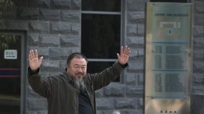 Chinese Activist artist Ai Weiwei waves to the journalists as he arrives to the Beijing No. 2 People's Intermediate Court in Beijing Thursday, Sept. 27, 2012. Chinese authorities on Thursday rejected Ai's second appeal of a $2.4 million tax fine, meaning his design company will have to pay the penalty. (AP Photo/Andy Wong)