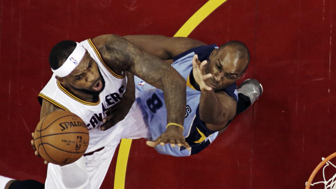 Cleveland Cavaliers' LeBron James, left, shoots over Memphis Grizzlies' Quincy Pondexter in the third quarter of a NBA basketball game Sunday, Dec. 21, 2014, in Cleveland. James scored 25 points and had 11 assists in the Cavaliers 105-91 win over Memphis. (AP Photo/Mark Duncan)