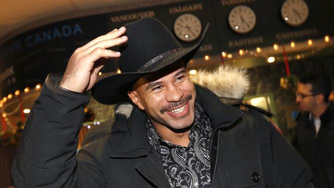 Calgary Stampeders' Cornish adjusts his cowboy hat after arriving at the airport for the start of the CFL's 102nd Grey Cup week in Vancouver.