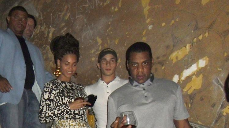 U.S. singer Beyonce, center, and her husband Jay-Z, right, walk down the stairs at La Guarida restaurant in Havana, Cuba, Wednesday, April 3, 2013. R&B's power couple is in Havana on their fifth wedding anniversary. (AP Photo/La Guarida)