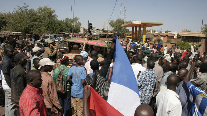 Residents of San in central Mali, some holding a French flag, gather around a convoy of French troops as they pass through San en route to Sevare, Mali, Friday, Jan. 18, 2013. French forces encircled a key Malian town on Friday to stop radical Islamists from striking closer to the capital, a French official said. The move to surround Diabaly came as French and Malian authorities said they had retaken Konna, the central city whose capture prompted the French military intervention last week.(AP Photo/Harouna Traore)