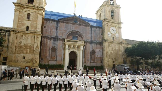 Britain's Prince William receives a national salute from the Armed Forces of Malta after arriving for High Mass at St John's Co-Cathedral in Valletta