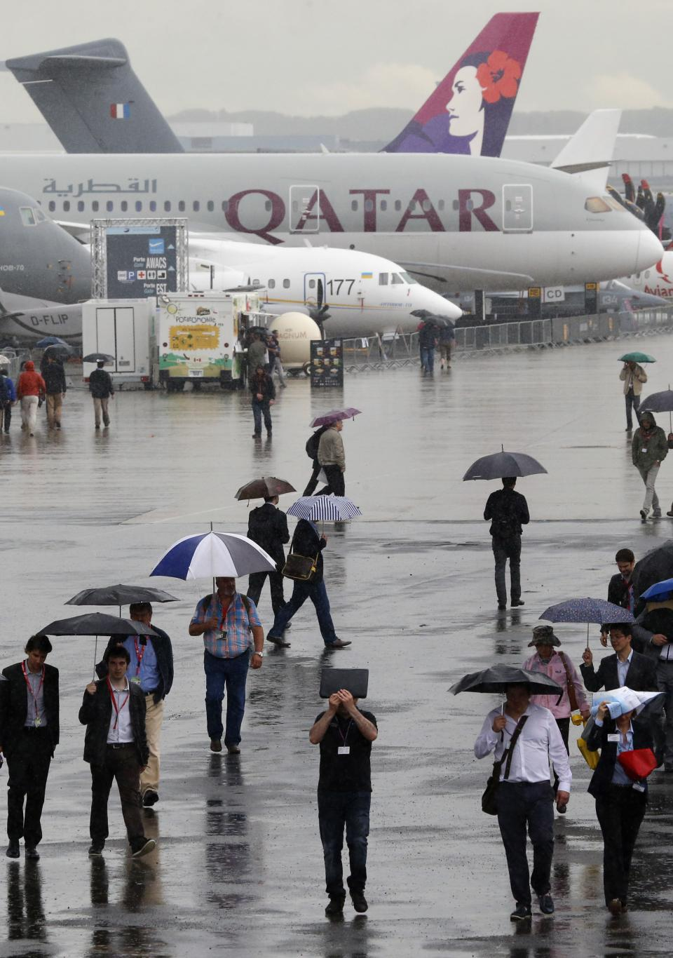 Visitors walk in the rain during the 50th Paris Air Show at Le Bourget airport, north of Paris, Thursday, June 20, 2013.  (AP Photo/Francois Mori)