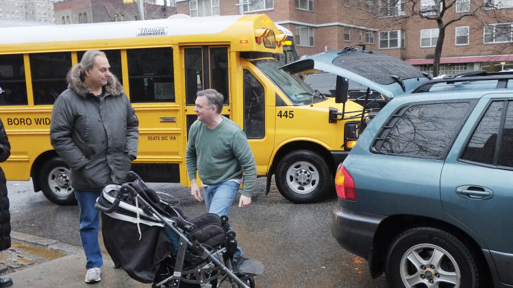 Peter Curry, center, unloads his daughter's wheel chair from his car after driving her to Public School 33, Wednesday, Jan. 16, 2013 in New York. She would normally be driven by school bus, according to her father. More than 8,000 New York City school bus drivers and aides went on strike over job protection Wednesday morning, leaving some 152,000 students, many disabled, trying to find other ways to get to school. (AP Photo/Mark Lennihan)