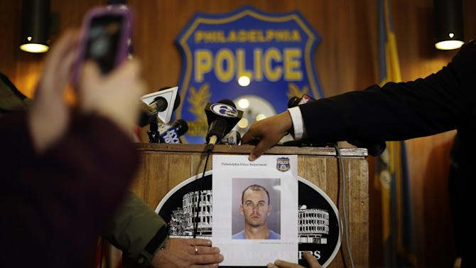 A photograph of 36-year-old Jason Smith is displayed at a news conference Thursday, Jan. 24, 2013, in Philadelphia. Homicide unit Capt. James Clark says Smith, an exterminator, has been charged with strangling a young Philadelphia doctor found bound and burned in her city row home. (AP Photo/Matt Rourke)