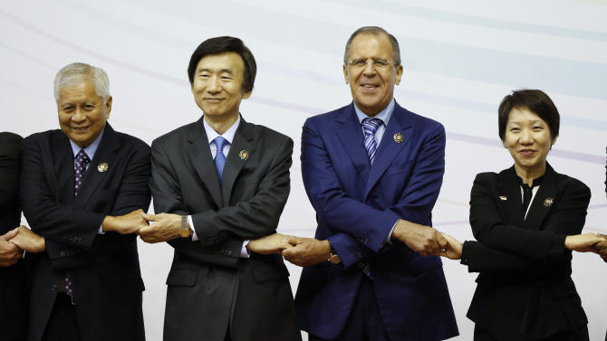 From lett to right, Philippine's Foreign Secretary Albert del Rosario, South Korea's Foreign Minister Yun Byung-se, Russia's Foreign Minister Sergei Lavrov and Singapore's Second Minister of Foreign Affair Grace Fu hold hands together during a group photo at the 3rd East Asia Summit (EAS) Foreign Ministers' Meeting in Bandar Seri Begawan, Brunei, Tuesday, July 2, 2013. (AP Photo/Vincent Thian)